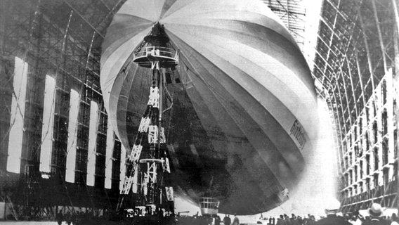 """Der Zeppelin LZ 129 """"Hindenburg"""" in einer Luftschiffhalle auf dem Frankfurter Rhein-Main-Flughafen im Jahr 1937. © picture-alliance / dpa Foto: Goettert"""