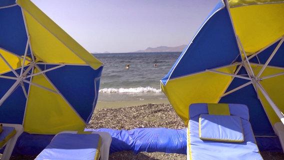 Sonnenschirme an einem Strand auf Kos.