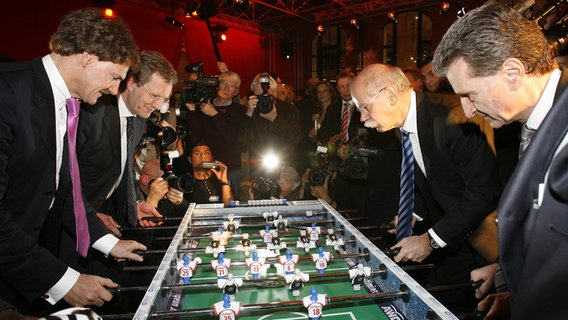 AWD Chef Carsten Machmeyer, der damalige niedersächsische Ministerpräsident Christian Wulff (CDU), der Vorstandsvorsitzende der Daimler AG, Dieter Zetsche, und Baden-Württembergs damaliger Ministerpräsident Günther Oettinger (CDU) spielen 2007 in Hannover beim Nord Süd Gipfel zusammen Tischfußball.