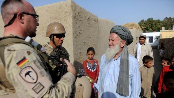Ein Bundeswehrsoldat und ein Dolmetscher in Bundeswehruniform sprechen nahe Kundus im Distrikt von Char Darreh mit Bewohnern. © dpa Foto:  Maurizio Gambarini