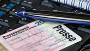 Presseausweis, Kugelschreiber und Ringbuch liegen auf einer Tastatur © picture alliance/chromorange Foto: CHROMORANGE / H. Richter
