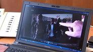 Eine Hand zeigt auf ein Videobild, das auf einem Laptop zu sehen ist.