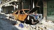 Ein ausgebranntes Autowrack in einer zerstörten Straße in Aleppo. © NDR/ARD