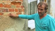 Roman Benter zeigt auf Risse in der Mauer.