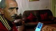 Salah T. hält ein Telefon mit dem Foto seines Sohnes in der Hand.