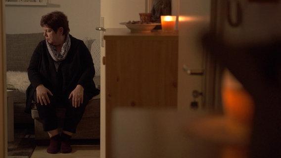 Ilona Franke mit Kerzen, im Dunkeln sitzend