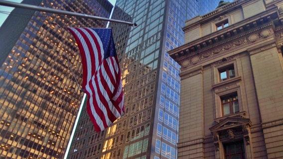 Eine US-Flagge vor einem Hochhaus